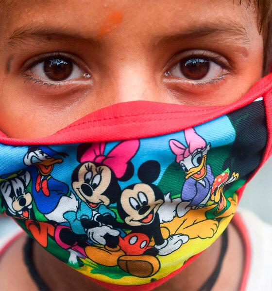 Kind mit Gesichtsmaske mit Disney-Figuren-Aufdruck