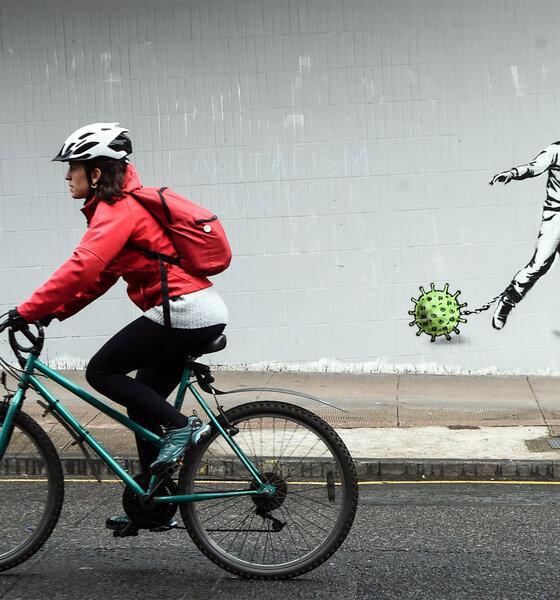 Radfahrer vor Graffiti mit Corona-Virus