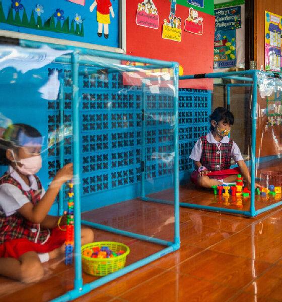 Thai-Mädchen spielen hinter Plastikfolien abgetrennten Spielbereichen
