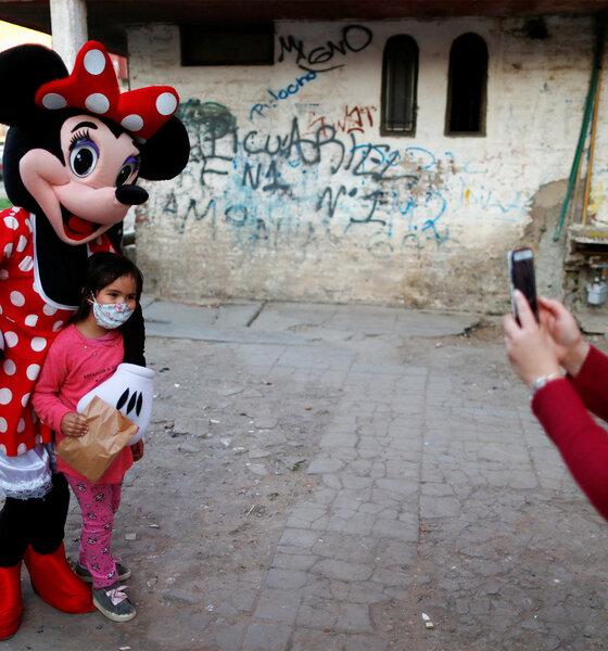 Mensch im Minnie-Mouse-Kostüm mit Kind während des Kindertages in Fuerte Apache in Buenos Aires, Argentinien