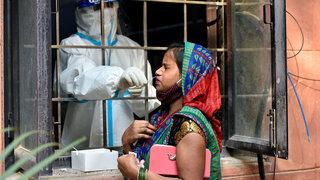 Gesundheitspersonal sammelt eine Tupferprobe für Coronavirus-Tests von einer Frau