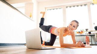 Ohne Sport drohen Entzugserscheinungen Frau Übungen zuhause Wohnzimmer Laptop Gesund Sportlich bleiben Coronavirus Lockdown