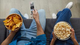 Ernährungswoche Corona und Ernährung Close up Paar sitzen Sofa Beine Snacks Naschen Fernbedienung TV Nachos Popcorn