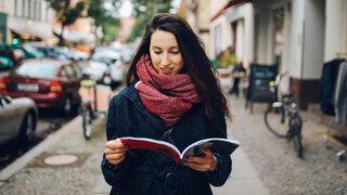 Mit Tagebuch und Musik Wie man seine Erinnerung wiederfindet Frau gehen gehend Lernen Heft Zeitschrift Lesen Spätherbst Kalt Stadt