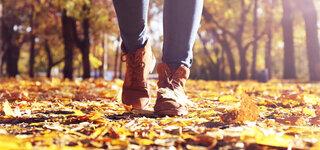 Coronavirus Winterblues Mit Bewegung gegensteuern Füße Close Herbst Blätter verwirbeln Gehen Stiefel Winterstiefel