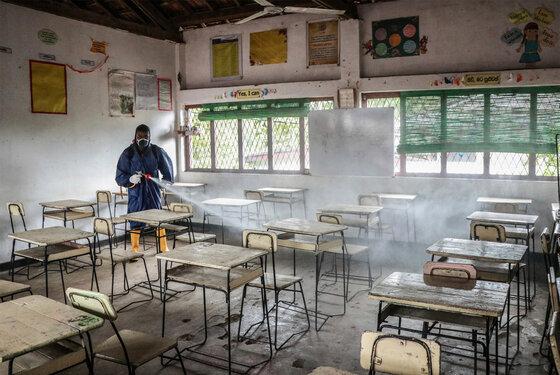 Gesundheitspersonal sprüht Desinfektionsmittel in einer leeren Schule in Gampaha