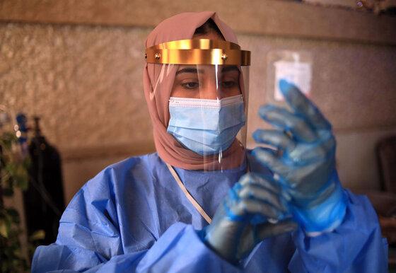 Kurdische irakische Krankenschwester in Schutzkleidung füllt eine Spritze