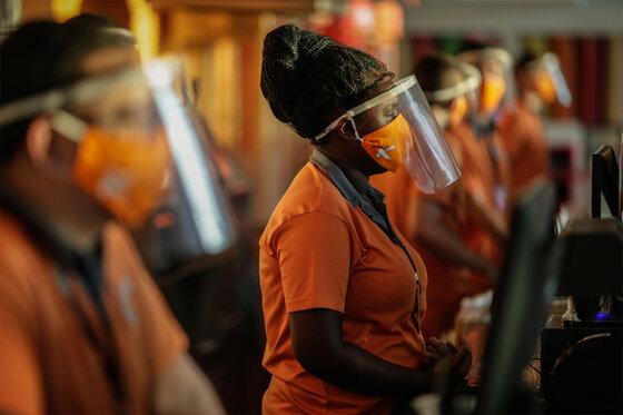 Mitarbeiter eines Kinos mit Gesichtsschutz