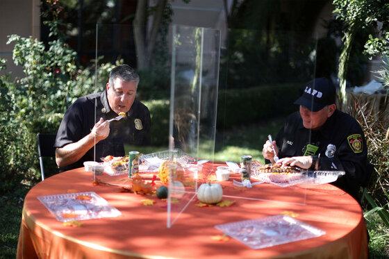 Zwei Feuerwehrmänner beim Mittagessen hinter Schutzglas-Aufstellern