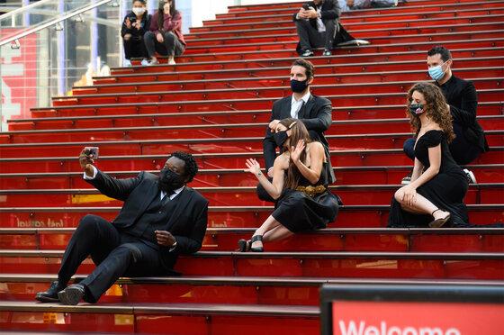 Menschen tragen Gesichtsmasken an den Roten Stufen am Times Square