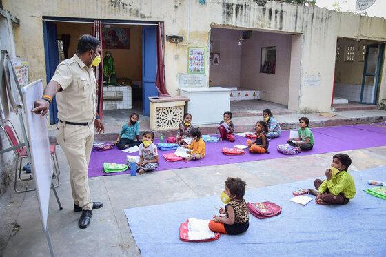 Delhi Polizist trägt eine Gesichtsmaske, während er Kinder in einer offenen Klasse während der Covid19-Pandemie unterrichtet.