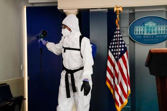 Reinigungspersonal des Weißen Hauses besprüht den Pressekonferenzraum