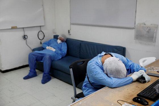 Medizinische Mitarbeiter in Schutzanzügen ruhen sich aus