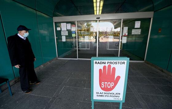 Ein Mann mit einer Gesichtsmaske wartet darauf, in das klinische Krankenhaus eingeliefert zu werden