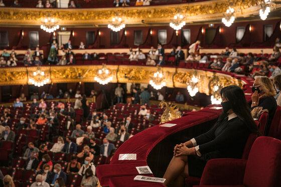 Menschen sitzen mit Abstand und Mund-Nasen-Schutz im Theater