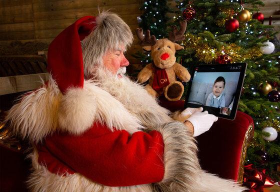 Weihnachtsmann spricht mit einem Kleinkind via Tablet