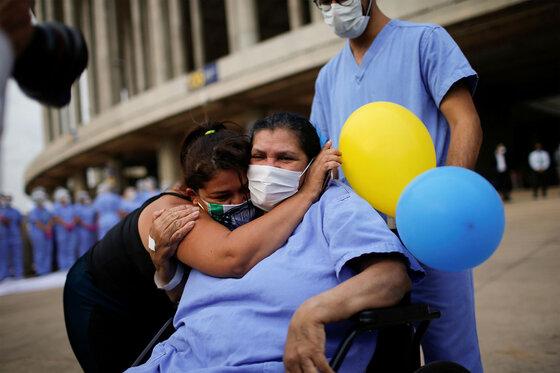 Frau wird umarmt, als sie das Krankenhaus verlässt, nachdem sie wegen der Coronavirus-Krankheit behandelt wurde