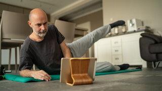 Coronavirus Sport Fitness zuhause Wohnzimmer YouTube Online Digital Übungen Mann Bart Anstrengung