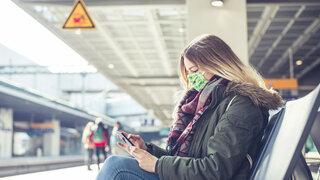 Bahnfahr Tipps zu Weihnachten Frau Warten Zug Handy Tippen Coronamaske Mund-Nase-Bedeckung konzentriert Bahnhof