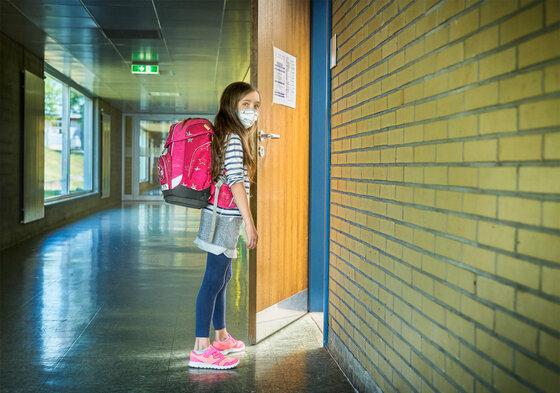 Schülerin mit Mundnasenschutz in der Schule