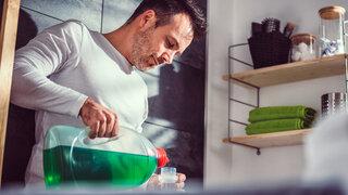 Zu viel Waschmittel kann Haut reizen Mann einfüllen Flüssiges Waschmaschine Waschen Hautreizung