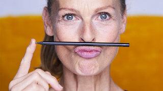 Gesichtsyoga: Seniorin macht Mimikübungen