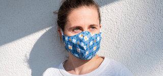 Alltagsmaske über OP Maske Frau Blümchen Muster Bunt Mund Nasen Schutz Coronavirus Hauswand Pullover