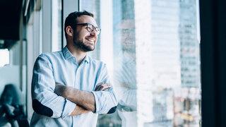 Mann mit Brille schaut aus dem Fenster