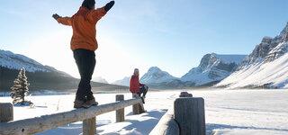 Was uns hilft durchzuhalten Winterspaziergang Tanzen Balancieren Ausgelassen Spaß Freude Paar Sonne Berge