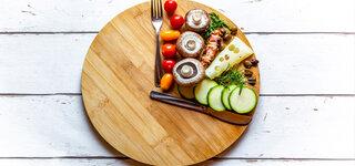Intervallfasten Teller Gemüse Symbolisch Uhr Uhrzeit Gabel Messer Brett Brotzeit einhalten Zeitrahmen