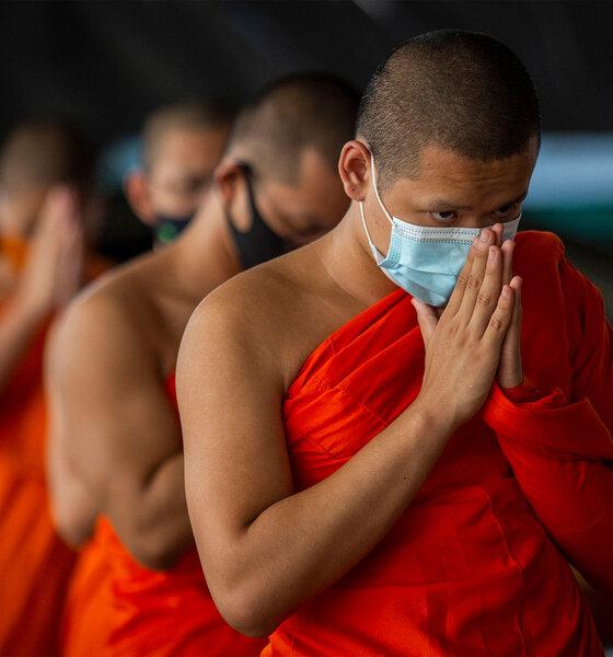 Thailändische Mönche sprechen ein Gebet, während sie Gesichtsmasken tragen