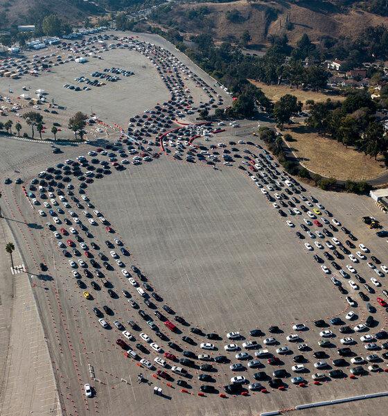 04.01.2021, USA, Los Angeles: Autofahrer warten auf einem Parkplatz, um einen Coronavirus-Test am Dodger Stadium zu machen.