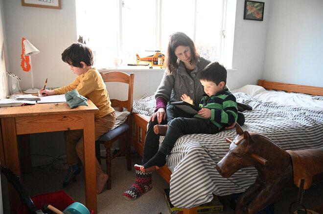 Mutter und ihre Kinder Zuhause beim Homeschooling