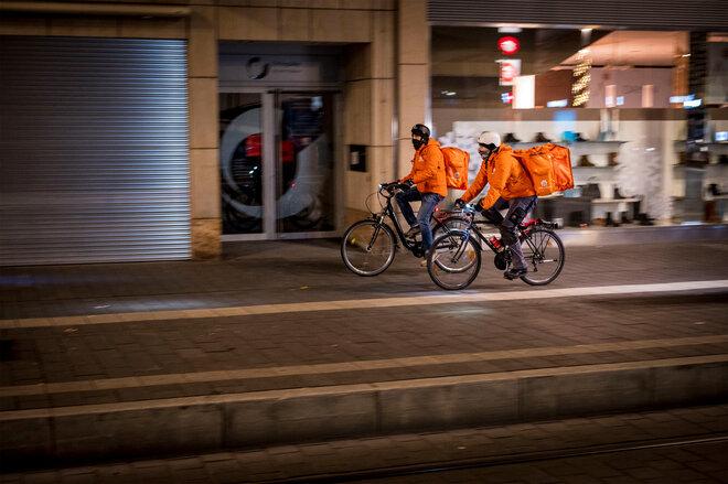 Lieferando-Fahrer auf Fahrrädern in einer leeren Fußgängerzone