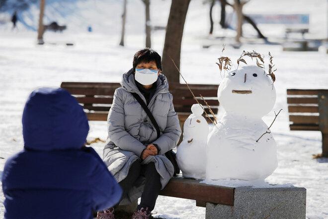 Frau mit Mundschutz auf einer Bank mit Schnnemann