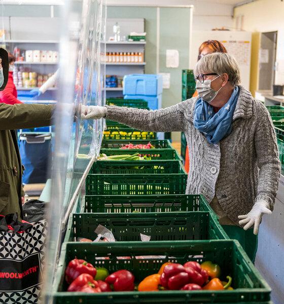 Bedürftige Menschen erhalten Lebensmittel, Obst und Gemüse von Freiwilligen an einer Tafel-Lebensmittelbank