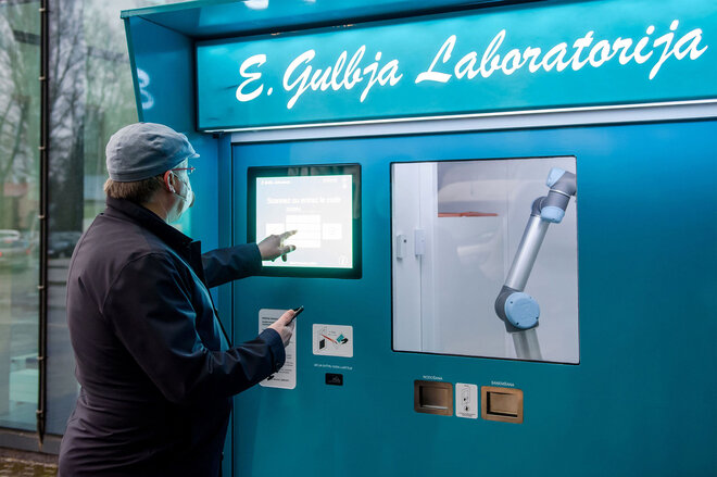 Mann gibt Code für einen Test für Coronavirus (Covid-19) auf einem Display einer kontaktlosen Teststation in Lettland ein