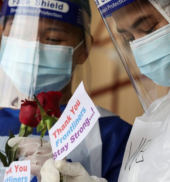 Medizinische Mitarbeiter mit Schutzmasken halten Rosen