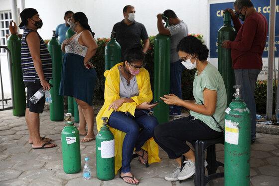 Menschen mit Masken warten vor einem Sauerstoff-Händler