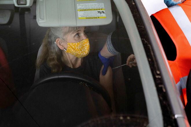 Frau erhält Impfstoff im Auto