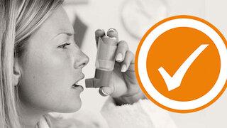 Frau inhaliert mit Asthmaspray