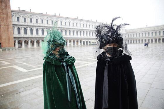 Zwei Menschen mit Karnevalsmasken und Gesichtsschutzmasken auf dem Markusplatz in Venedig