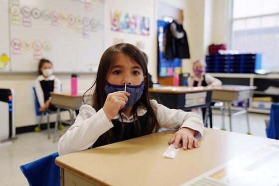 Schulkinder tupfen sich ab und testen sich auf COVID-19