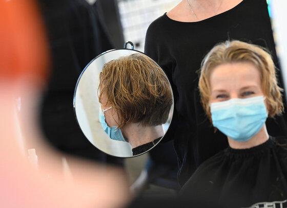 Frau mit Mundschutz beim Friseur
