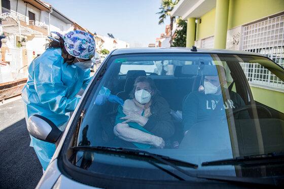 Seniorin wird in einem Auto geimpft