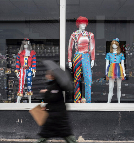 Mensch mit Schirm vor einem Schaufenster mit Karnevalsverkleidungen