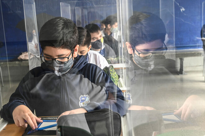 Schüler im Unterricht hinter Plexiglas