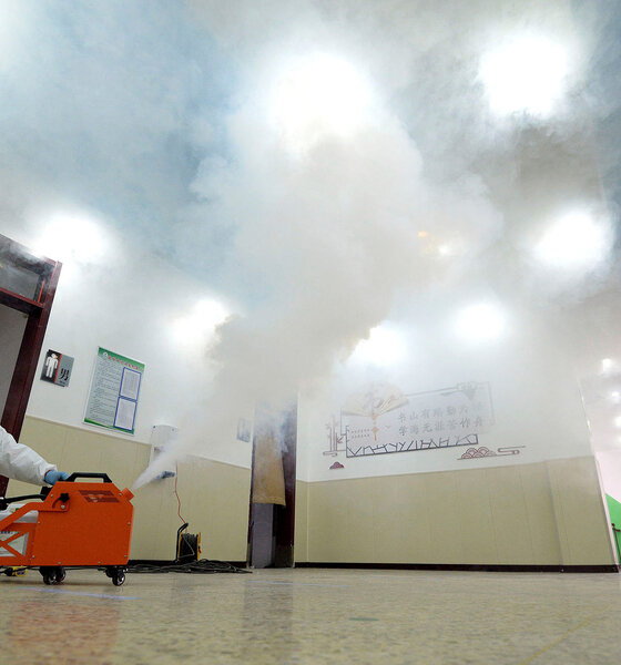 Mitarbeiter desinfizieren Lehrzimmer