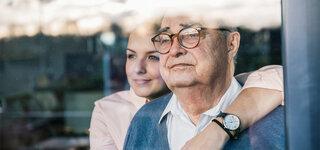 Senior und Tochter sehen aus dem Fenster