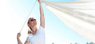 Frau spannt das Sonnensegel auf